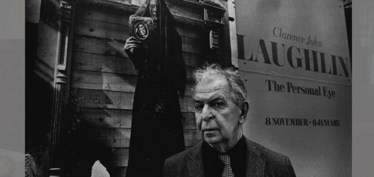 Clarence John Laughlin standing in front of one of his exhibitions.