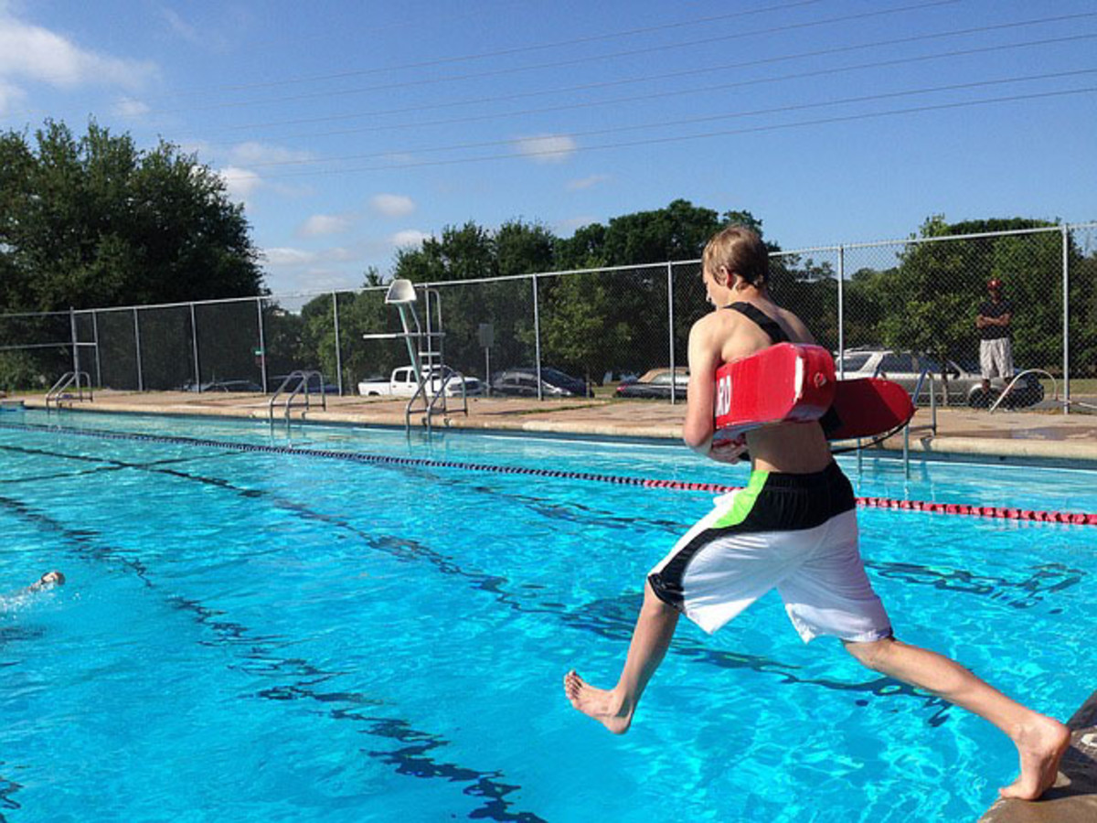 Life guard in action at a swimming pool location.