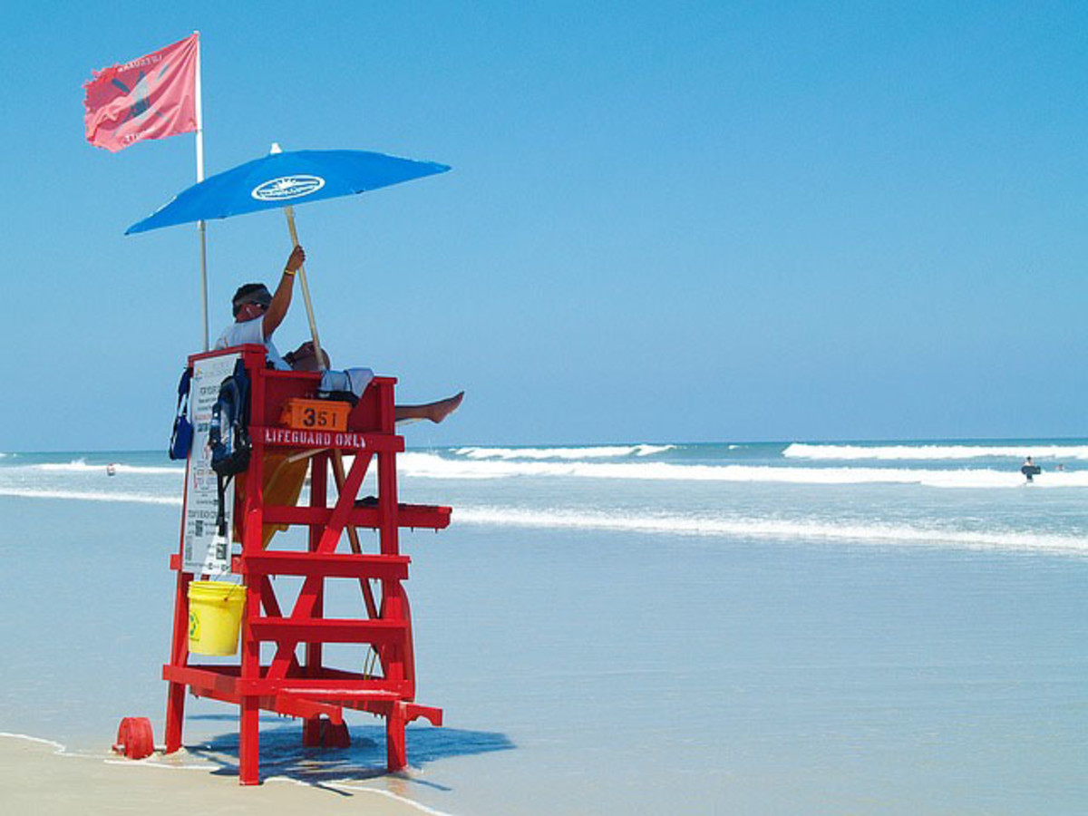 Life guard at his station watching swimmers in ocean.