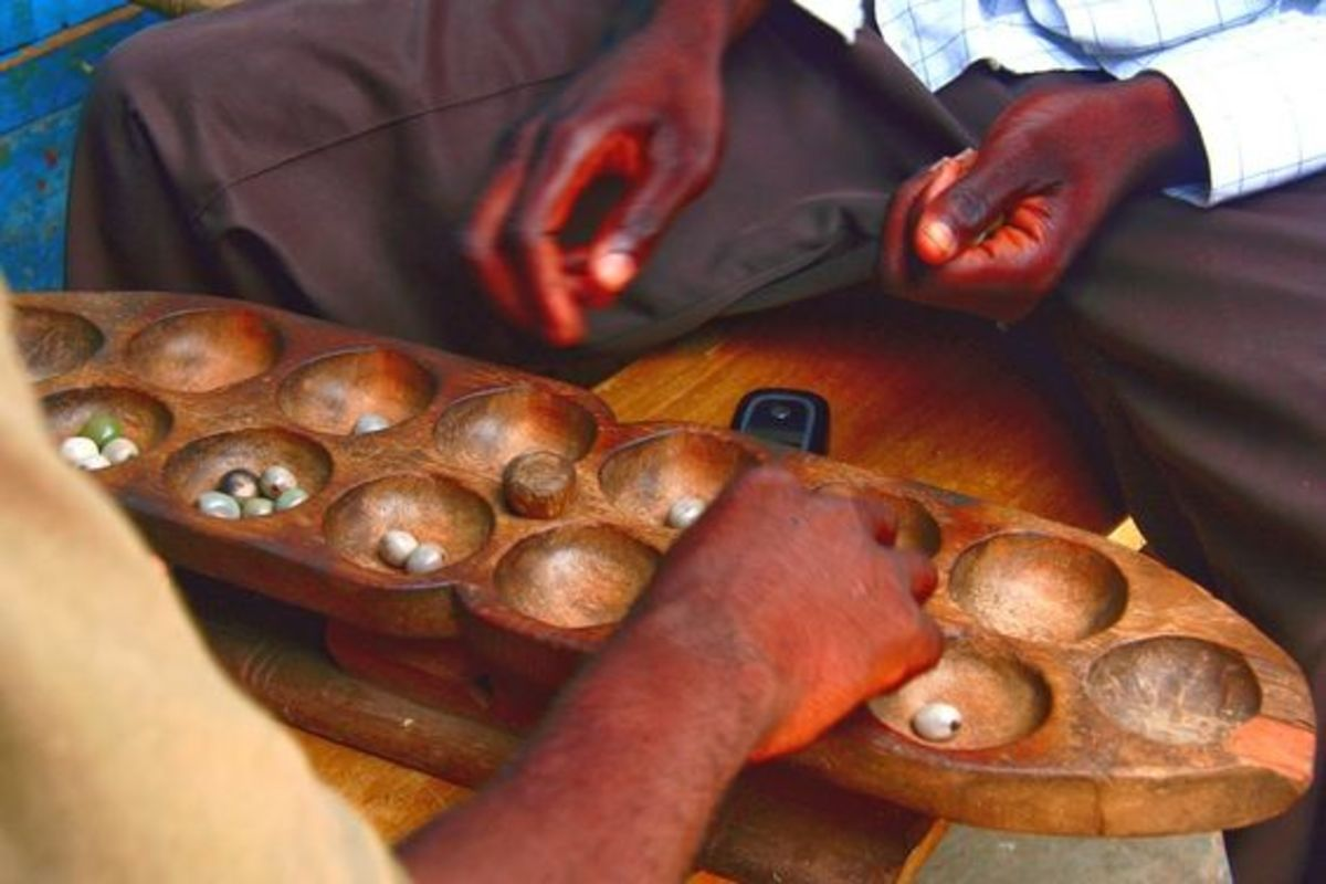 Game of Mancala being played on a carved out game board.