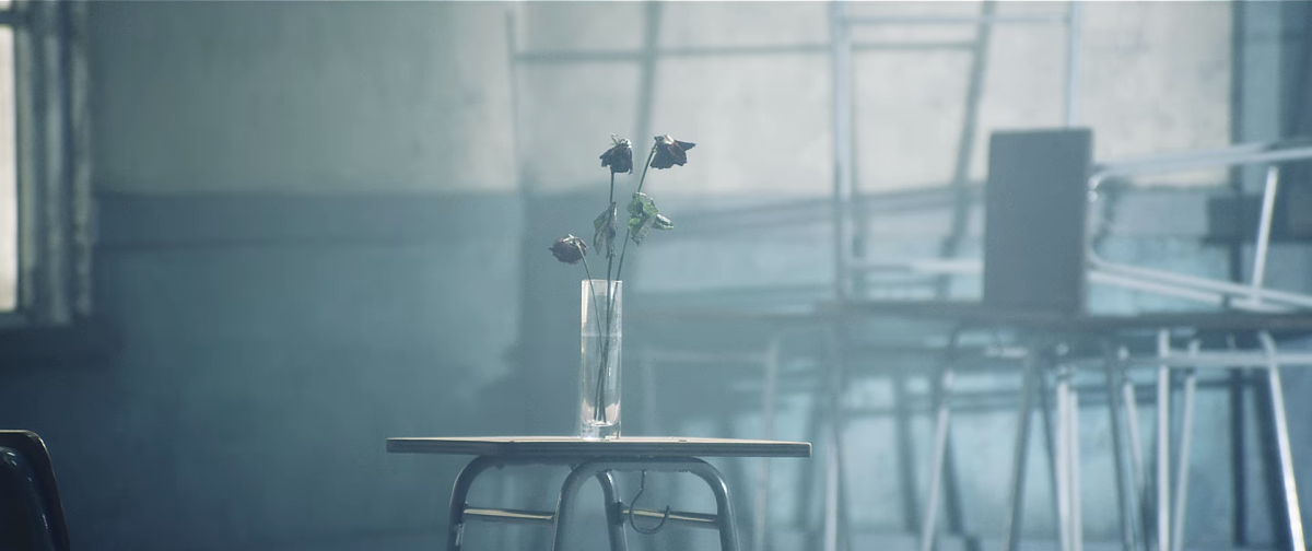 The vase with withered roses on the desk.