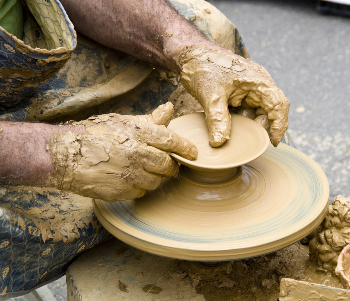 A pair of hands sculpting clay for pottery.