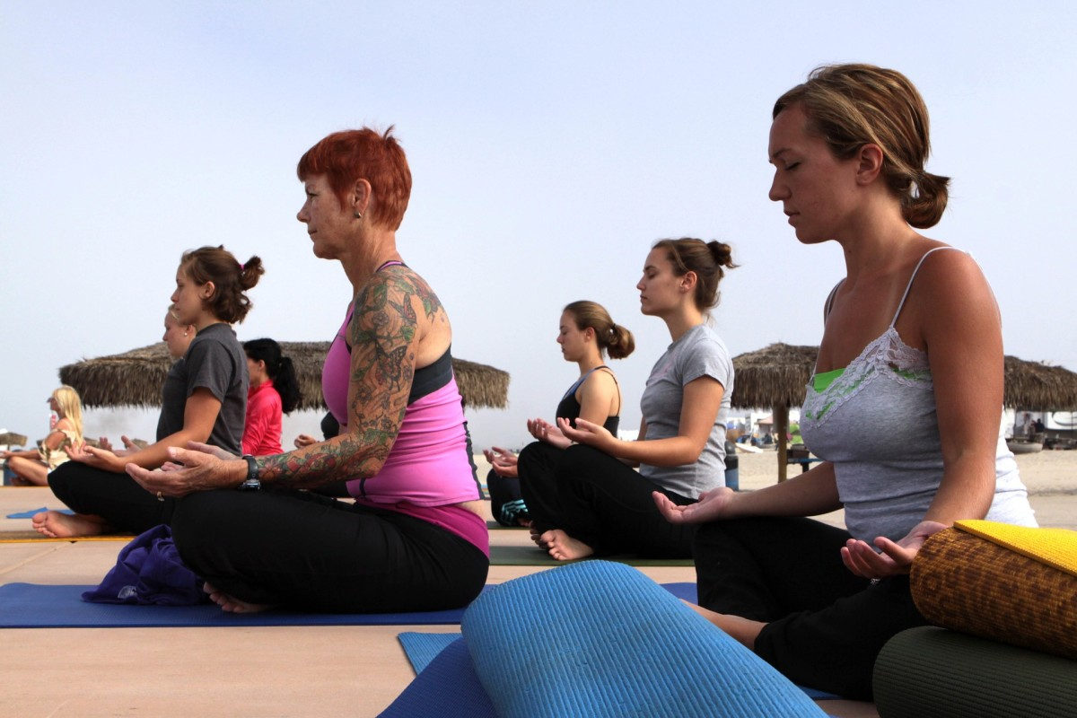 A group of women practicing yoga meditation at the beach.