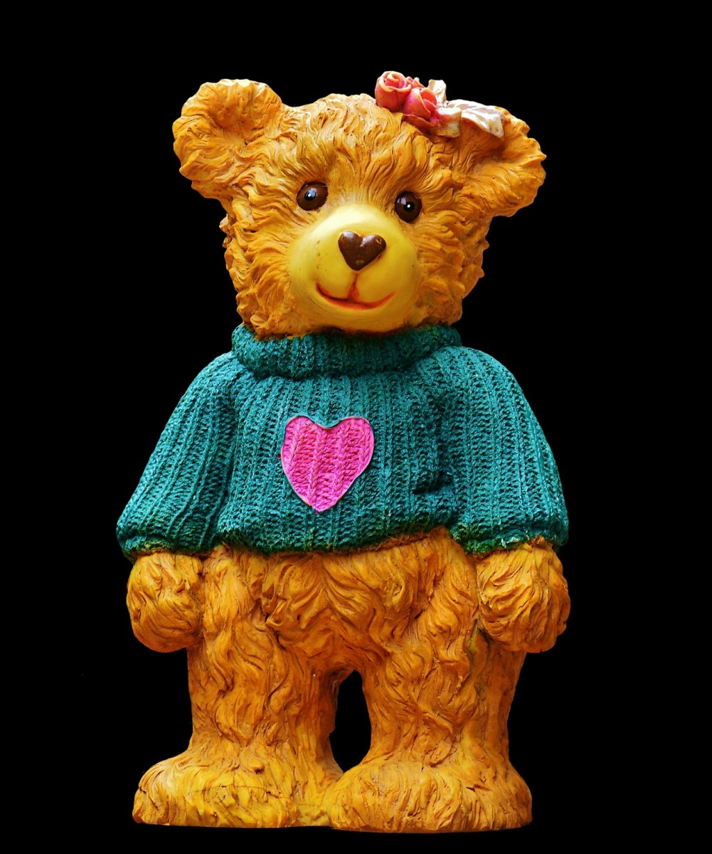 A stone teddy bear wearing a hand knitted sweater.