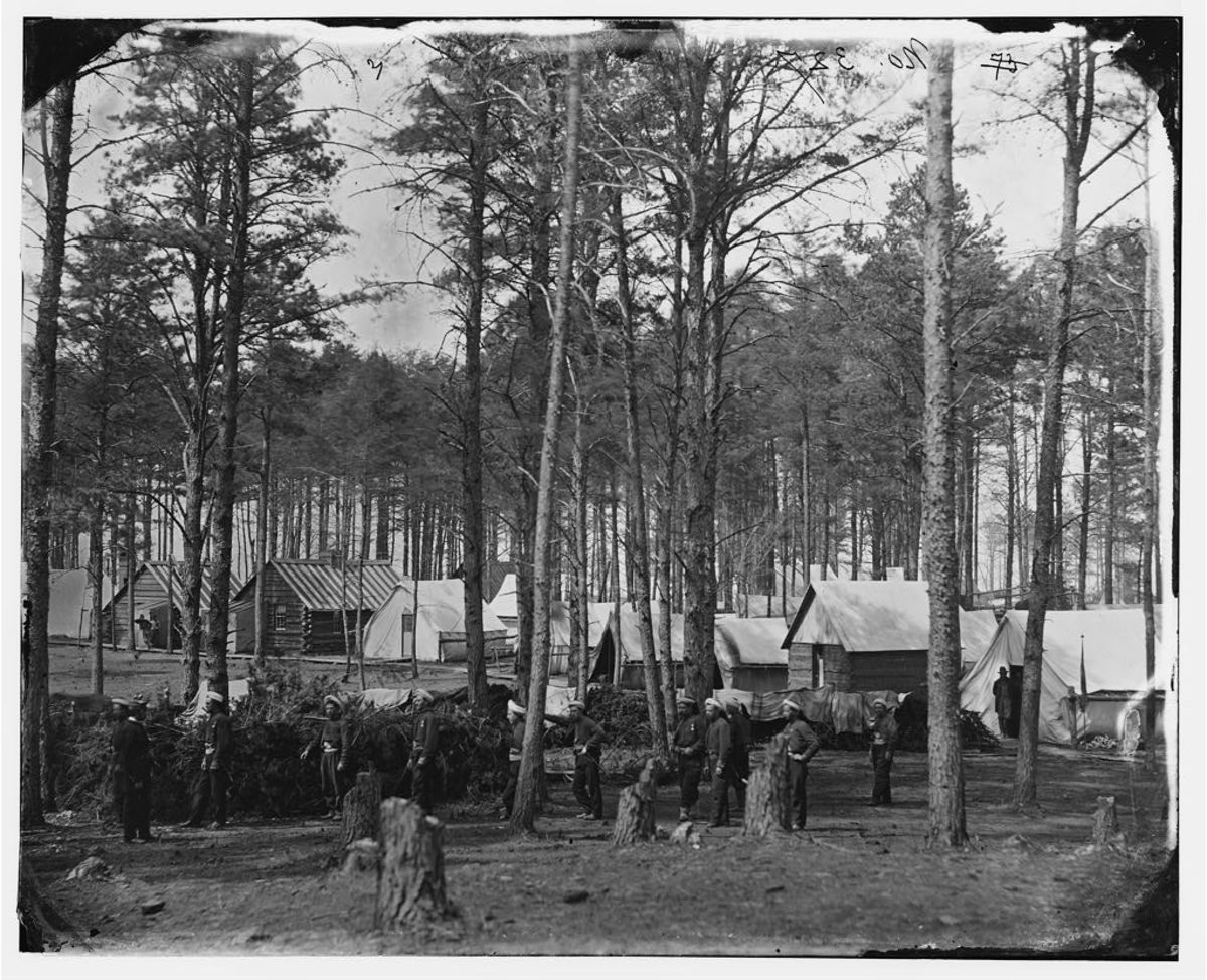 Winter camp at Brandy Station. Note the blankets drying on a line near the tents. Notice the tree stumps in the foreground where trees were felled for building cabins or for use as firewood.