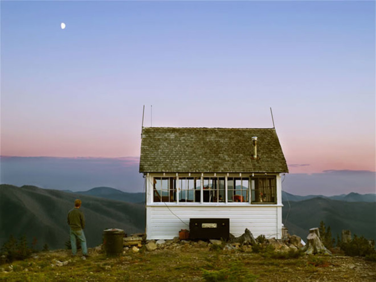 Mountain side home overlooking a mountain range at dusk. Here is a home with a 360 degree window view that shows the surrounding mountain ranges and gives a bigger feel over the home.