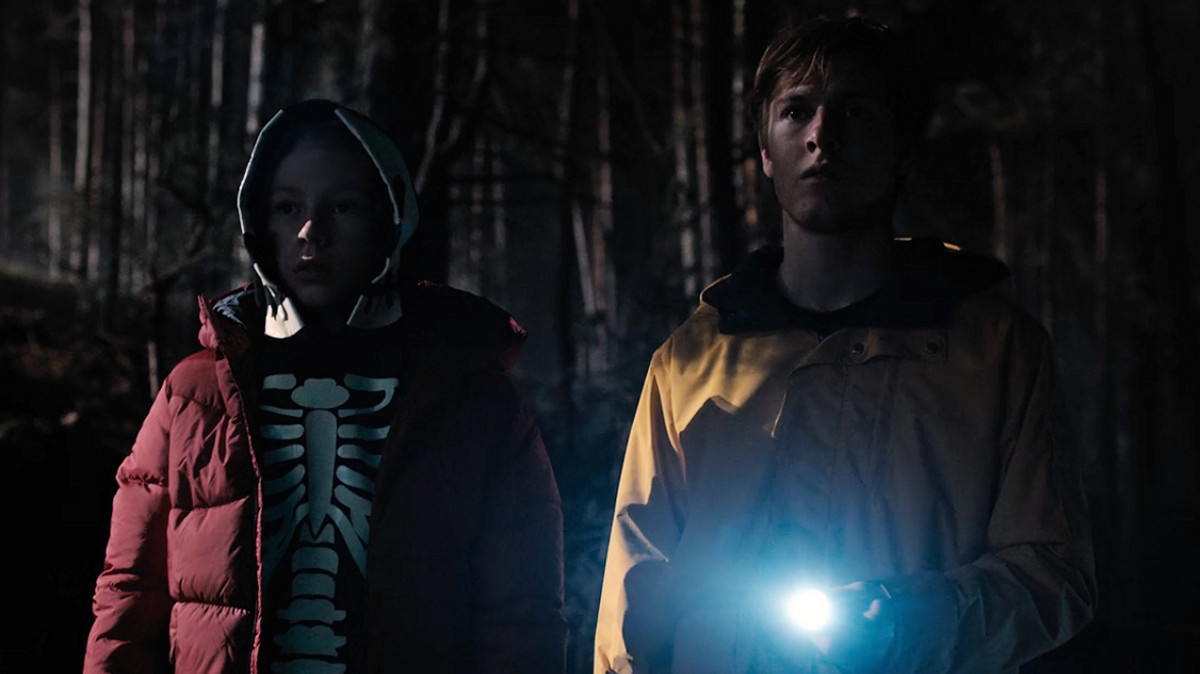 Mikkel Nielsen and Jonas Kahnwald stare toward the opening of Winden Cave in 'Dark' (2017), a Netflix Original Series.
