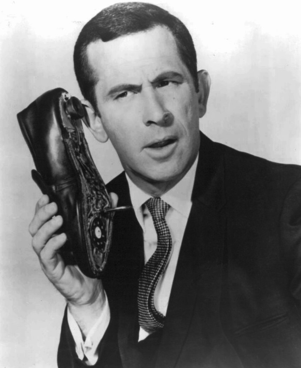 Maxwell Smart, Secret Agent 86 (Don Adams), talking into his shoe phone.  The shoe phone is a series trademark.