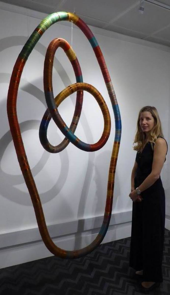 Curator Claudia Trosso stands beside Inka Space, a mobile structure made with copper and thread.