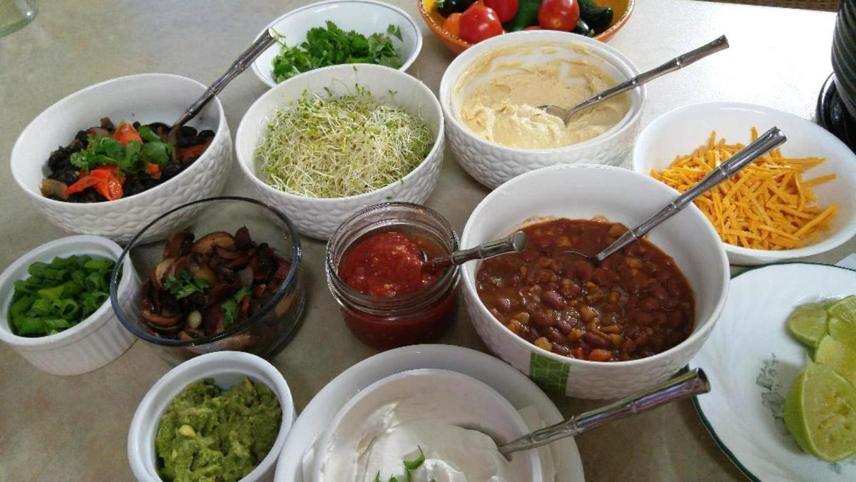 Examples of some of the toppings for a 'vegan' Baked Potato Bar: 2 kinds of bean dishes, cilantro, green onion, tofutti sour cream, salsa, hummus, guacamole, garlic mushrooms, sauerkraut, kimchee, vegan cheese shreds, alfalfa sprouts.