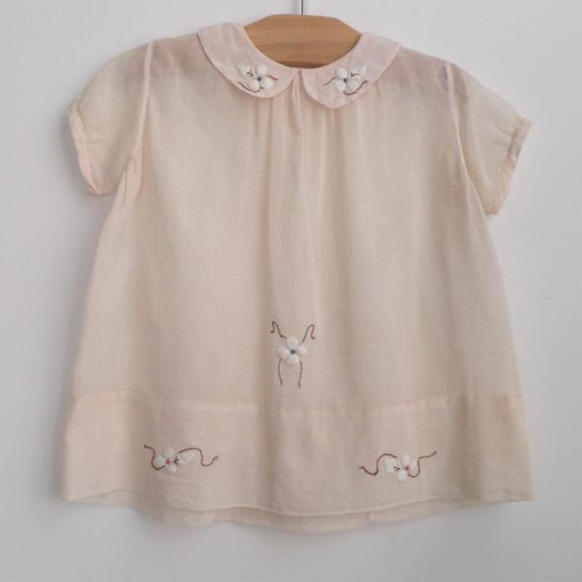 """Belle Heir"" dogwood dress c. 1940    pale peach lightweight cotton gauze    smock dress with peter pan collar.    finished with beautiful dogwood     applique + embroidery.    one snap closure in back.    Sh: 10.5""    L: 15""                Item No:"