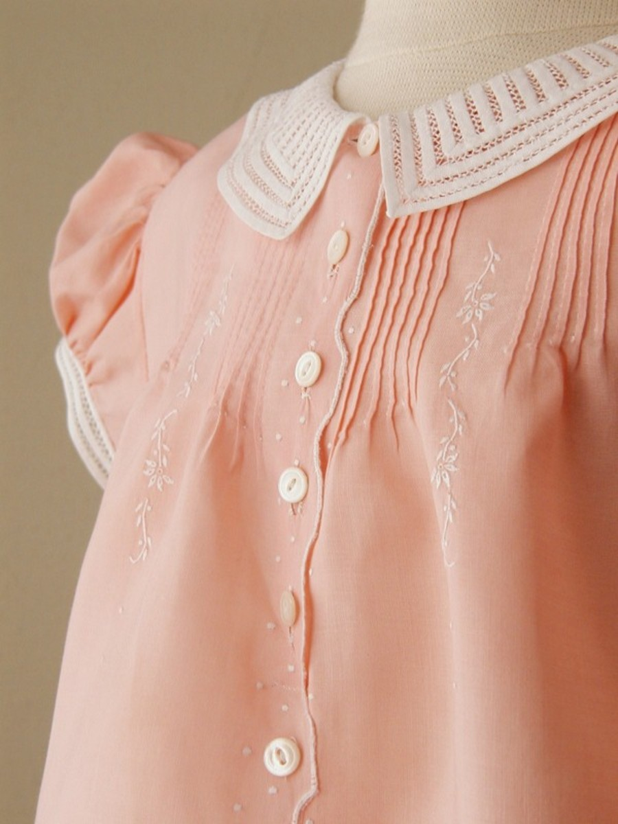From Mrs. Bird: Salmon Cotton Dress      C.1940.                     Unusual salmon color.  Pintucks, embroidered flowers and dots, scallop design, and 13 buttons down the middle. Constructed by hand. French seams throughout. Collar and cuffs careful