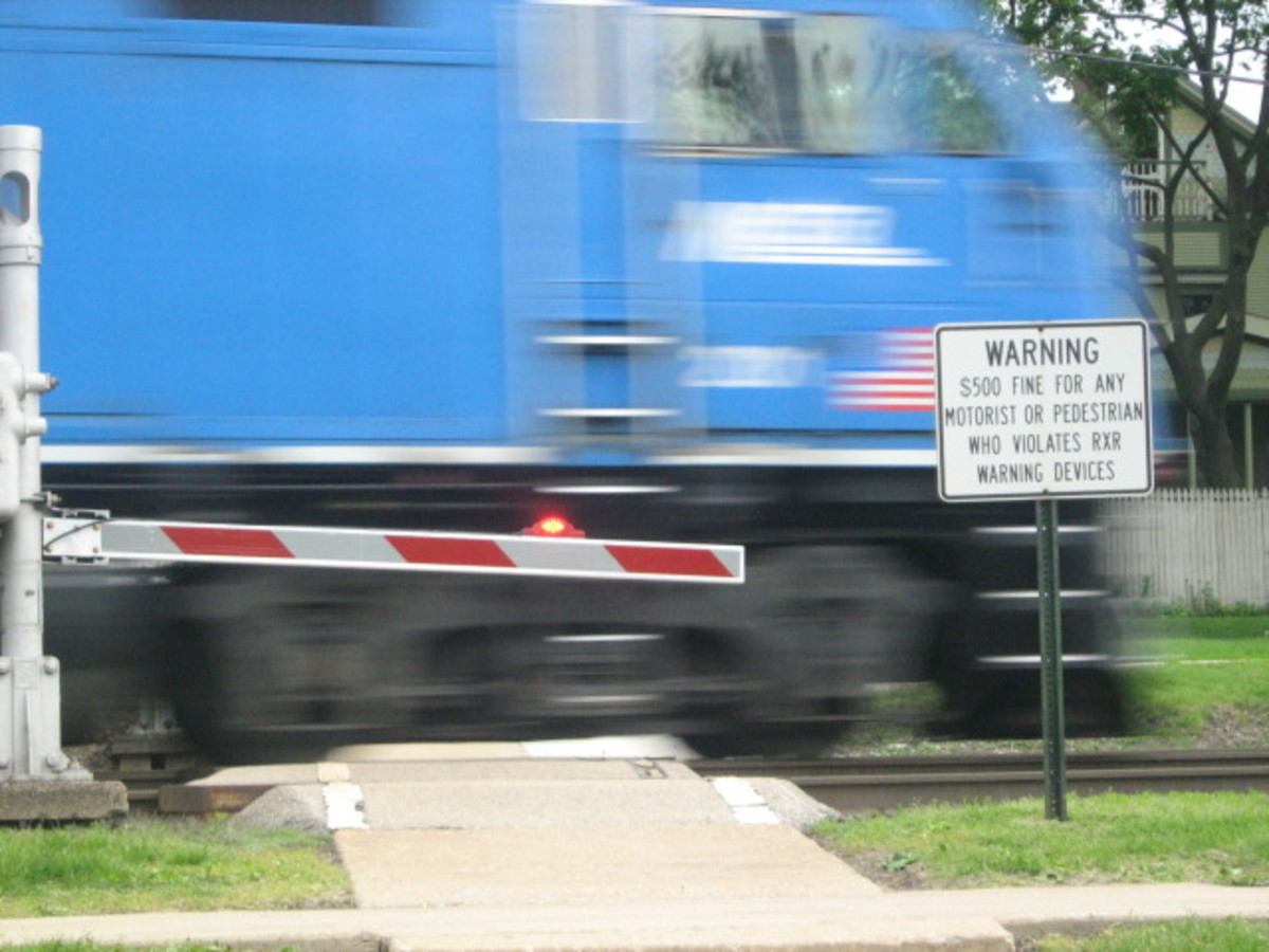 Pedestrian crosswalk near Downtown Hinsdale with the gate down, lights flashing, and a warning to not cross when trains are approaching