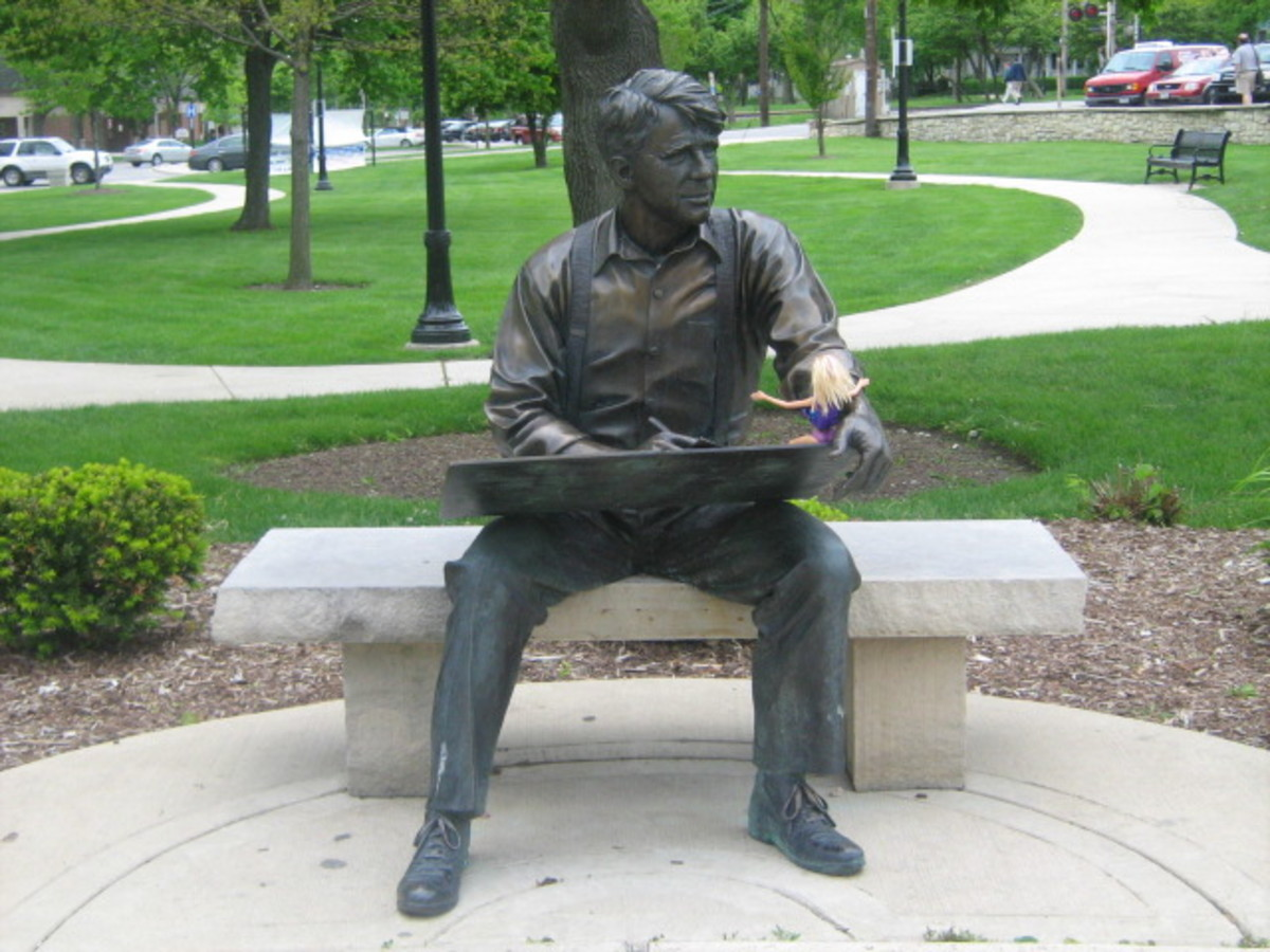 Robert Frost statue sitting, facing the water fountain, in the Downtown Hinsdale Park