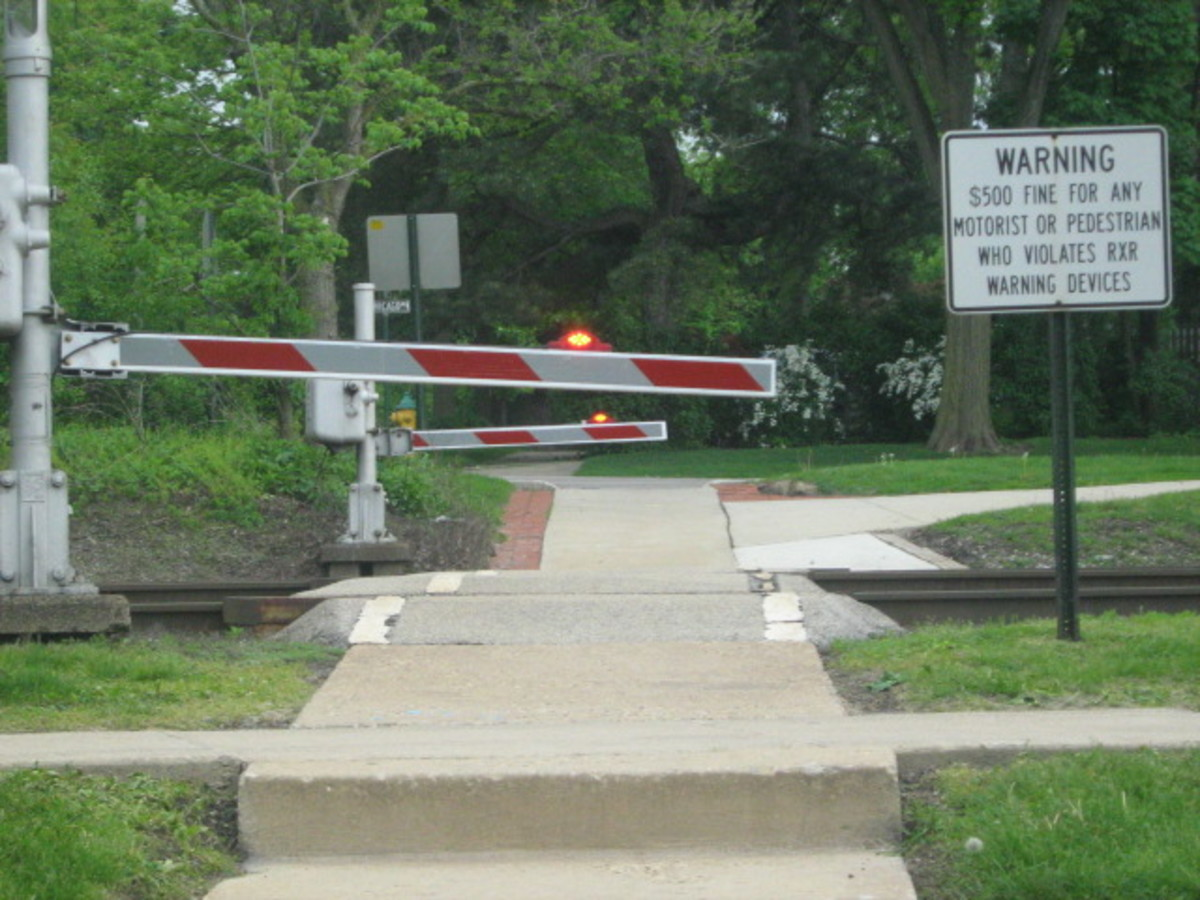 A pedestrian crosswalk near Downtown Hinsdale with the gate down, lights flashing, as the Metra train nears from Chicago