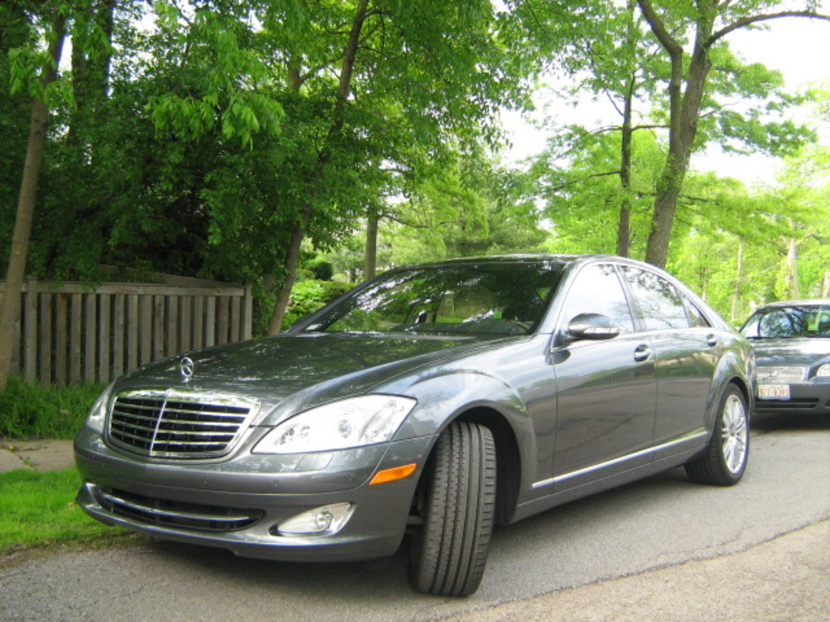 Many nice cars are seen driving through Hinsdale and parked in front of residences