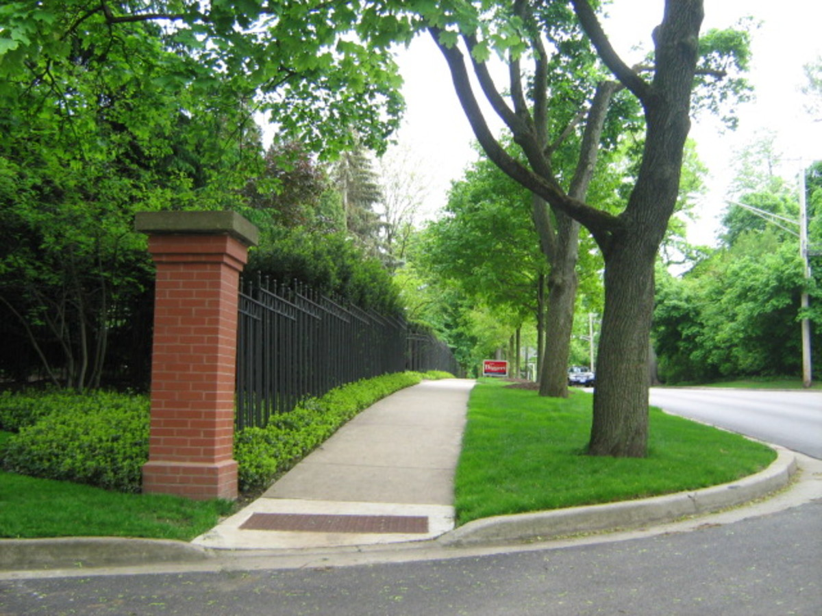 A block of iron fencing and greenery blocks the view of one of the biggest mansions in Hinsdale