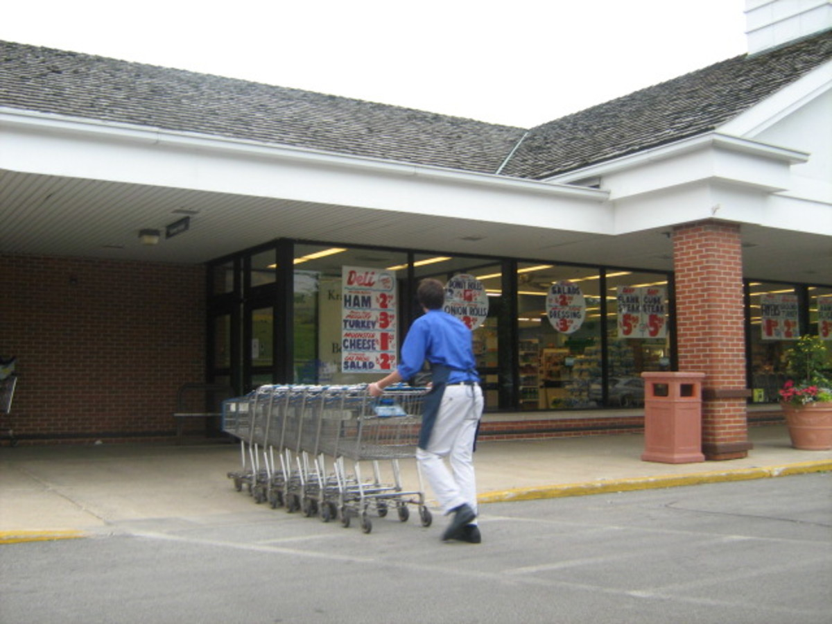 Young man retrieving shopping carts at an independently-owned supermarket - wearing white slacks, dress shirt, and a tie