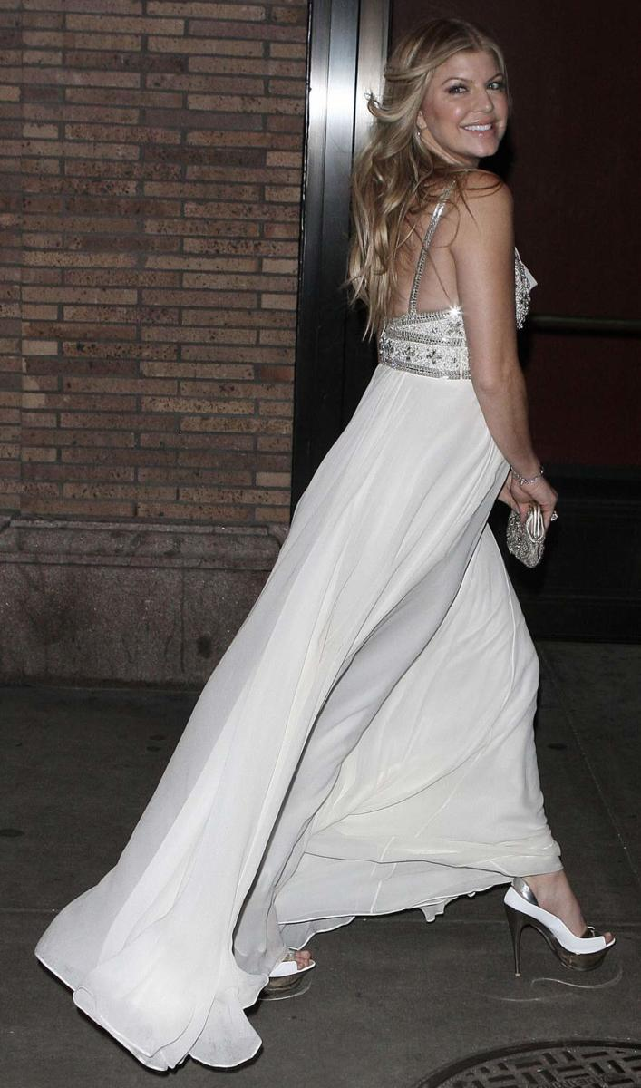 Fergie in a long flowing white dress and towering platform high heels