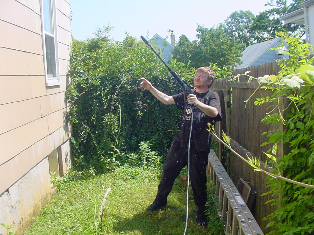 Power washing the house : Dave would have better control of the power washer if he used both hands.