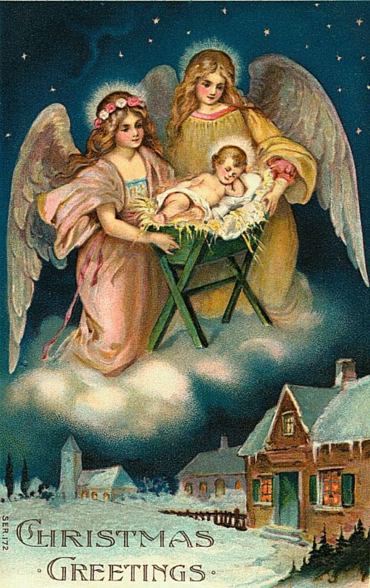 Two vintage angels with baby Jesus, village below