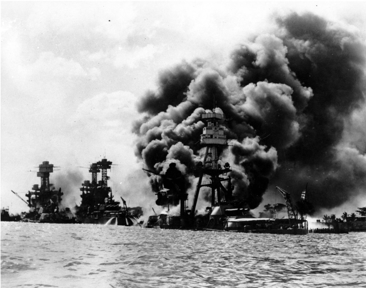 Japan bombs the US Pacific Fleet  in Pearl Harbor -- US warships burning