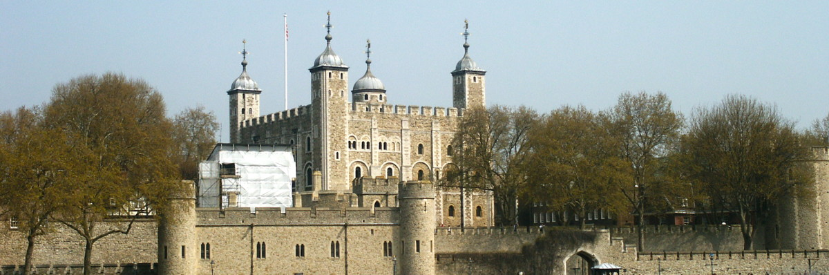 The White Tower rising above and behind the Outer Wall, visible from the Thames River.
