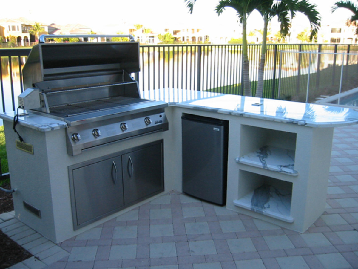 Free standing grill island with polished marble for additional storage and seating.