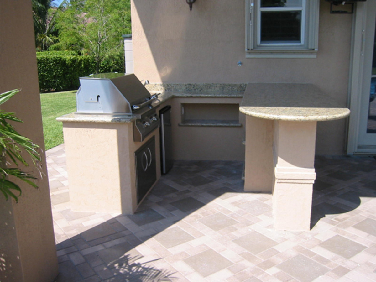 U-shaped design outdoor kitchen with separate seating area.