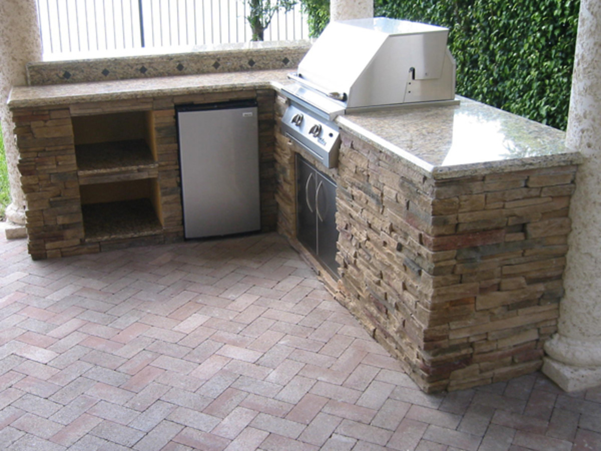 Grill island with 90 degree counter adds space for refrigerator and space for plates, napkins and cups