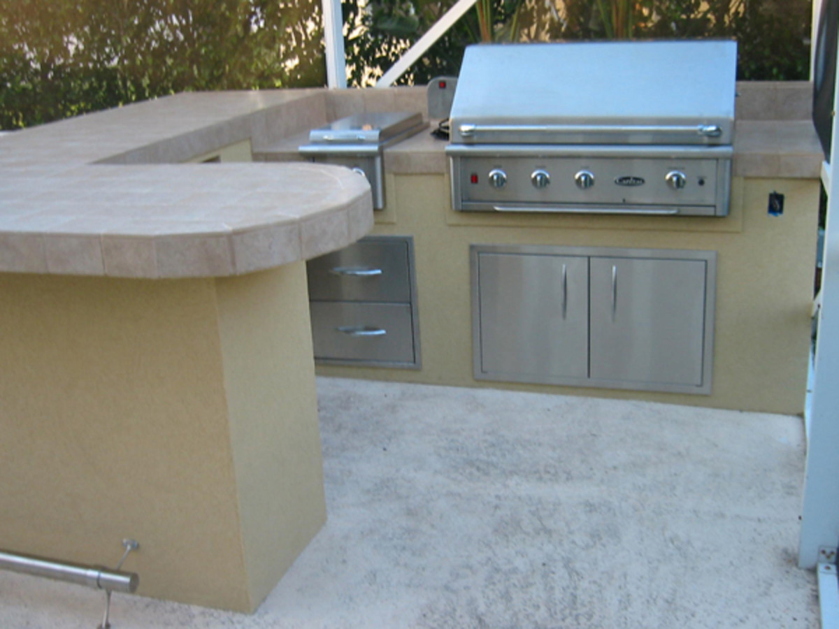 Outdoor kitchen with a lot of room to prep, serve and sit.  No longer carrying food to the other side of the yard everything is in one location.