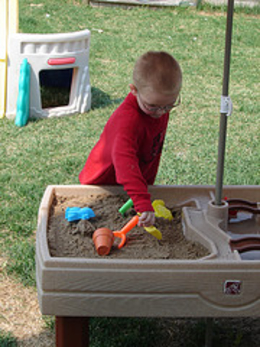 An infant experimenting with sand