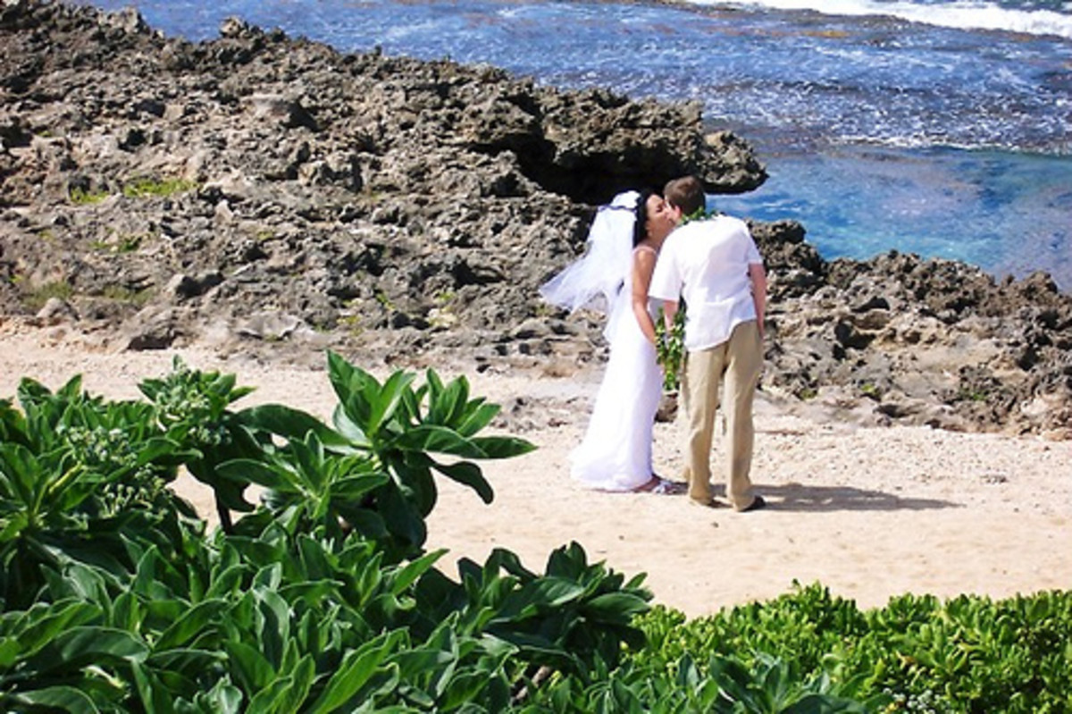 Newlyweds steal a kiss on the beach in Hawaii.