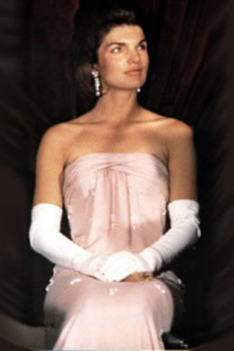 Jackie Kennedy sitting pretty in pink with long white gloves