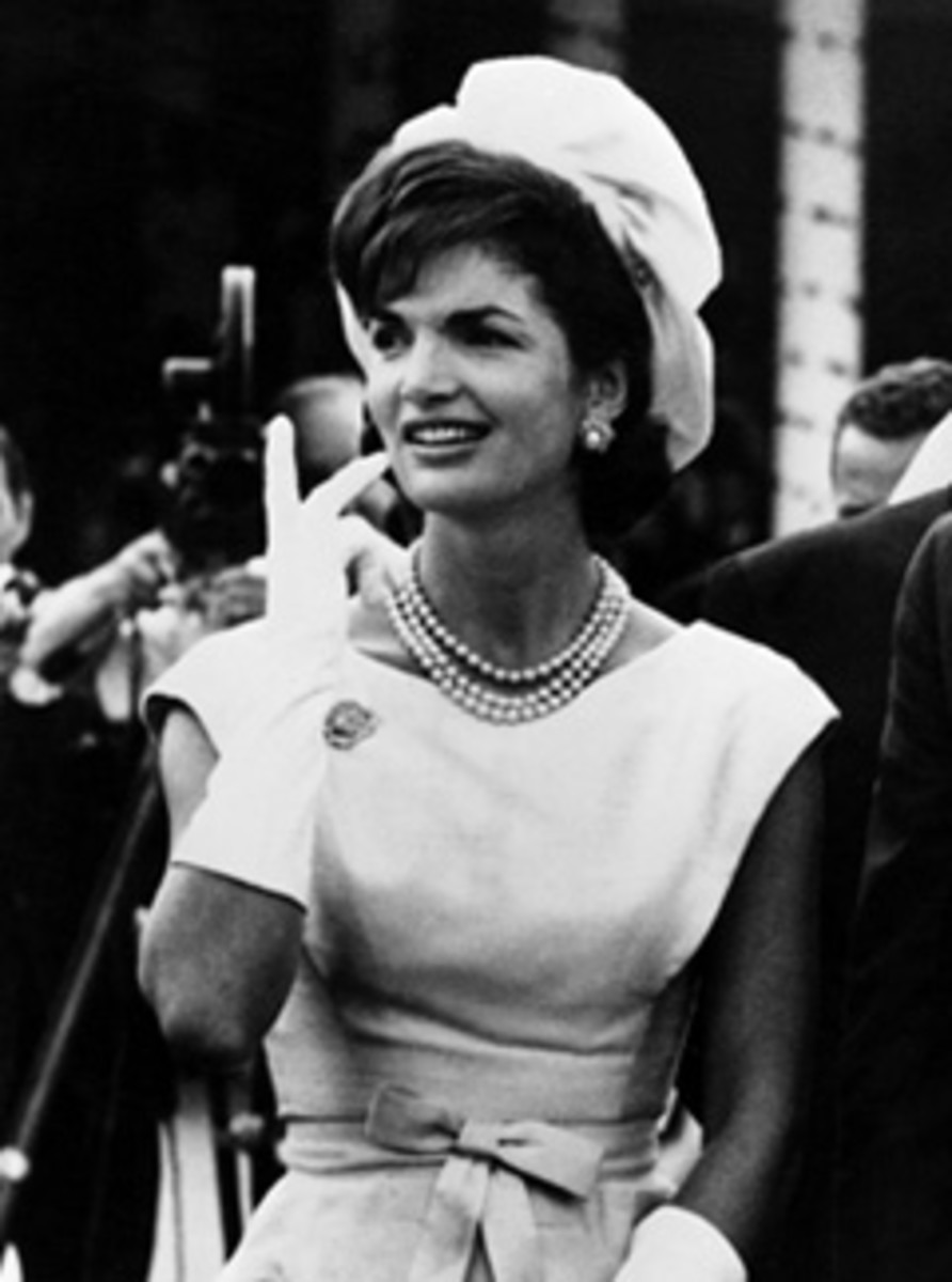 Jackie Kennedy wearing gloves, hat and her iconic three strand pearl necklace
