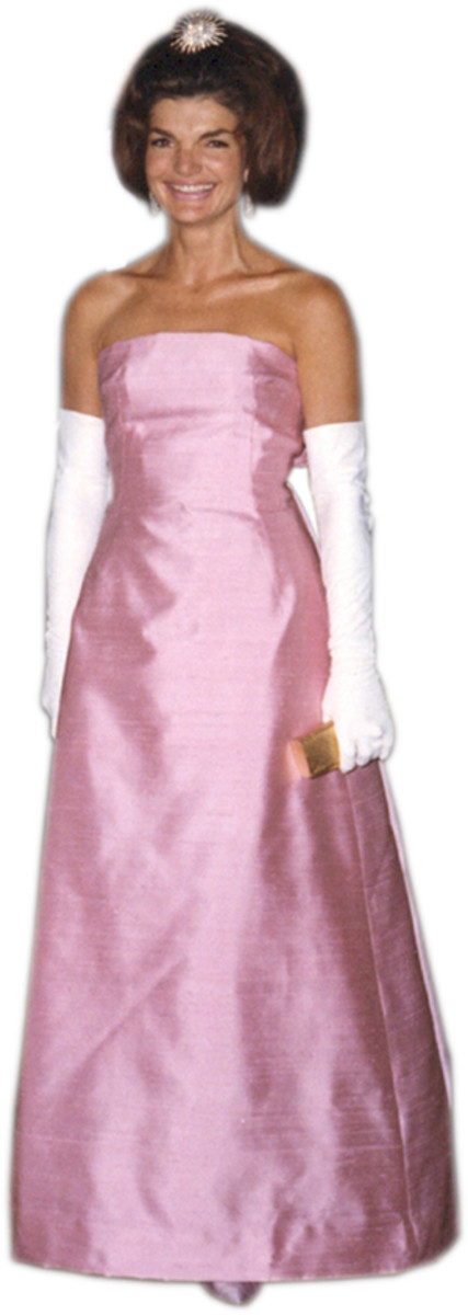 Jackie Kennedy wearing gloves in a pink evening gown