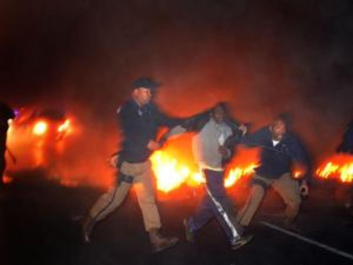 A protester is arrested by metro police officers after a group of about 40 people burned tires and barricaded a section  of the N2 early this morning, July 14th 2011