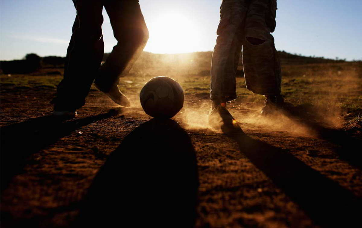 Children play soccer in a field in Erasmia Township in South Africa. Children are still playing, without boots, grass and and proper soccer clothing, despite the success of the World Cup Tournament in south Africa
