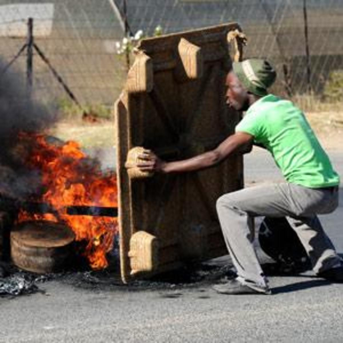 A protester shields himself from rubber bullets fired by the police during  in Zandspruit settlement in northwest Johannesburg violent service delivery protest