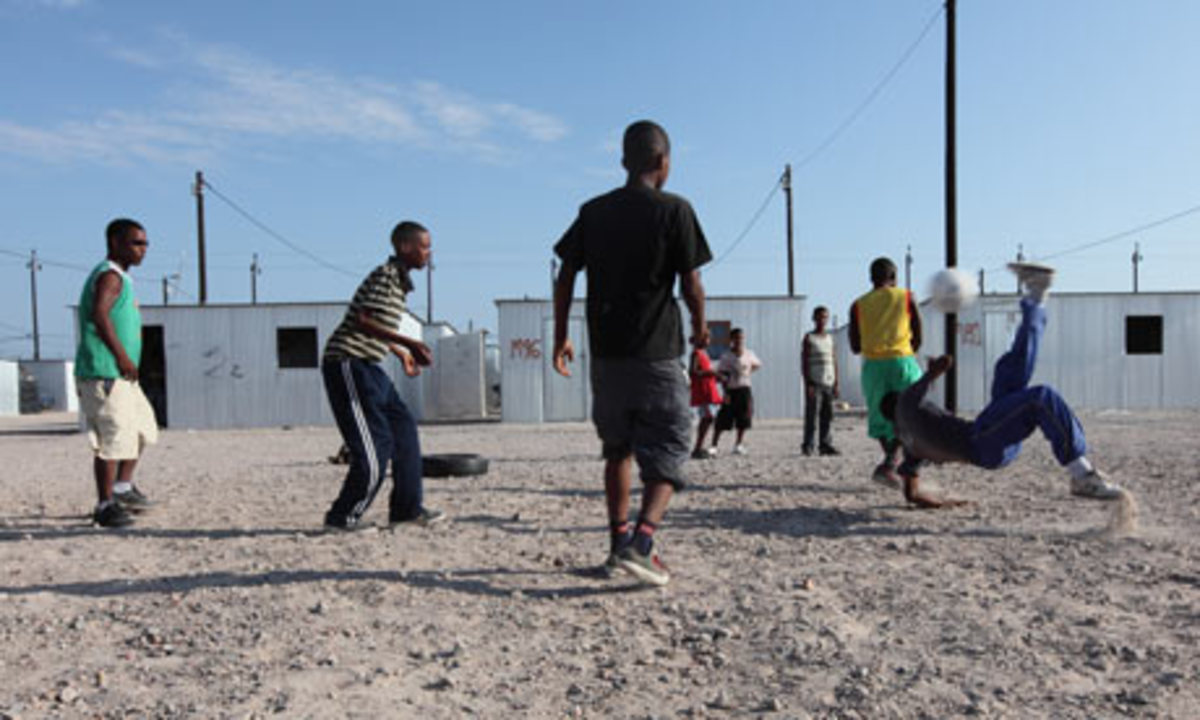 Youths playing football in Blikkiesdorp, Cape Town. Photograph