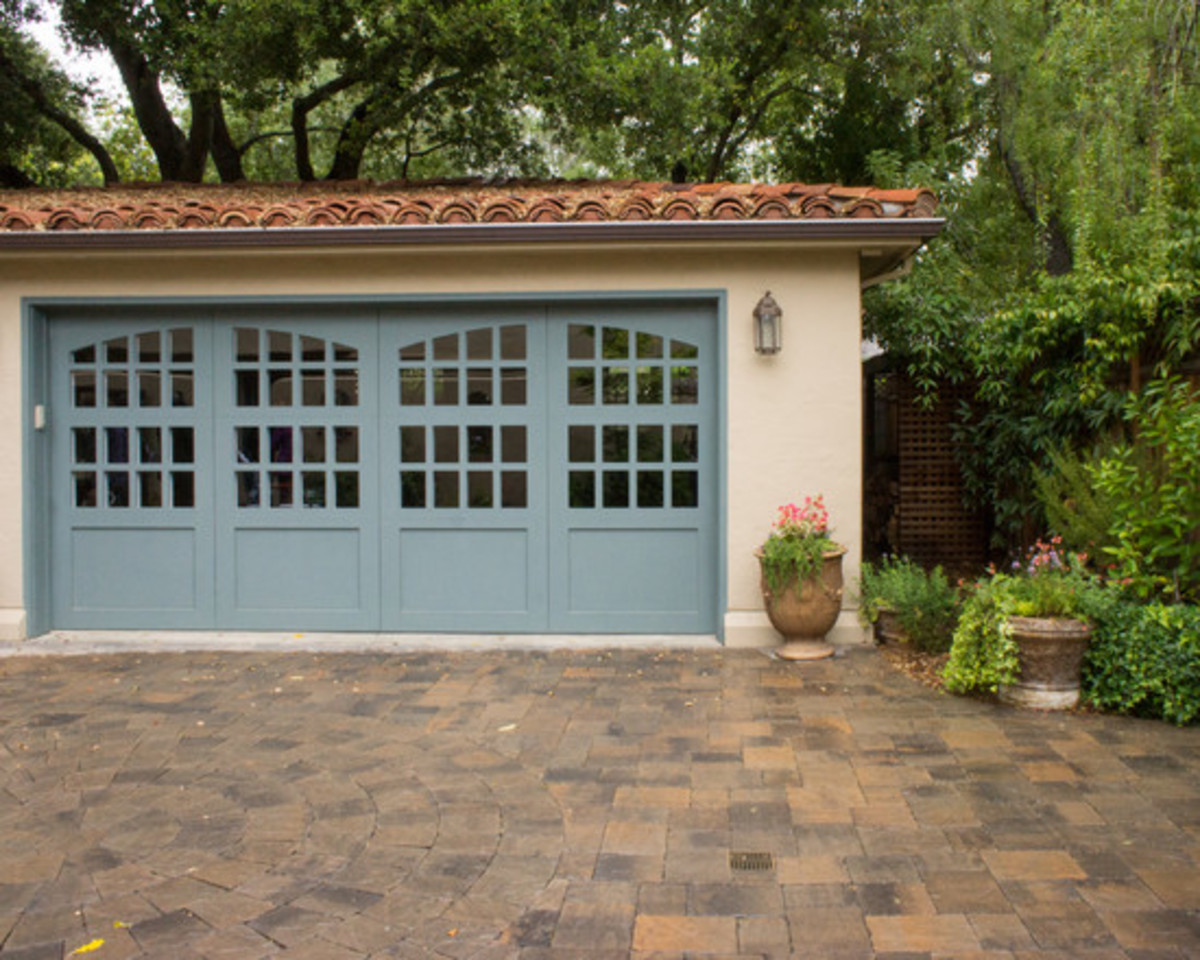 beautiful Mediterranean garage doors with blue paint and arched glass windows and clay tile rool