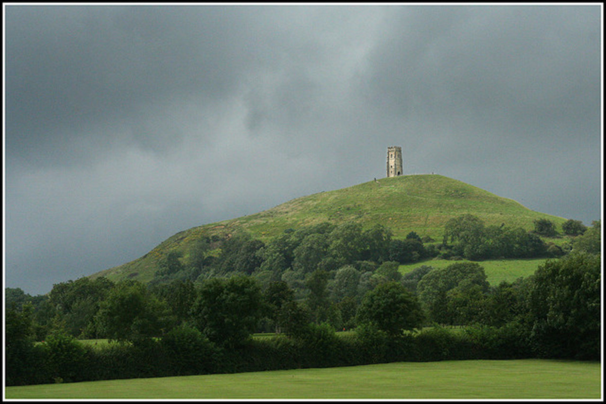 Dark skies and sunlight at Glastonbury Tor.
