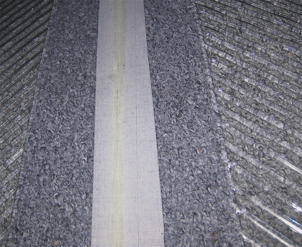 close-up of sticky side of gaffing tape and carpet seen through the heavy duty clear plastic floor mat