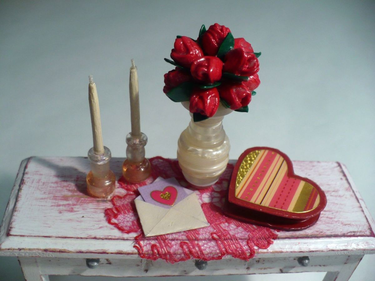 Learn how  to make your own dollhouse miniatures for Valentine's Day: miniature candlesticks and taper candles, a miniature Valentine card, a miniature vase with a dozen tiny roses, and a miniature heart-shaped box of chocolates.