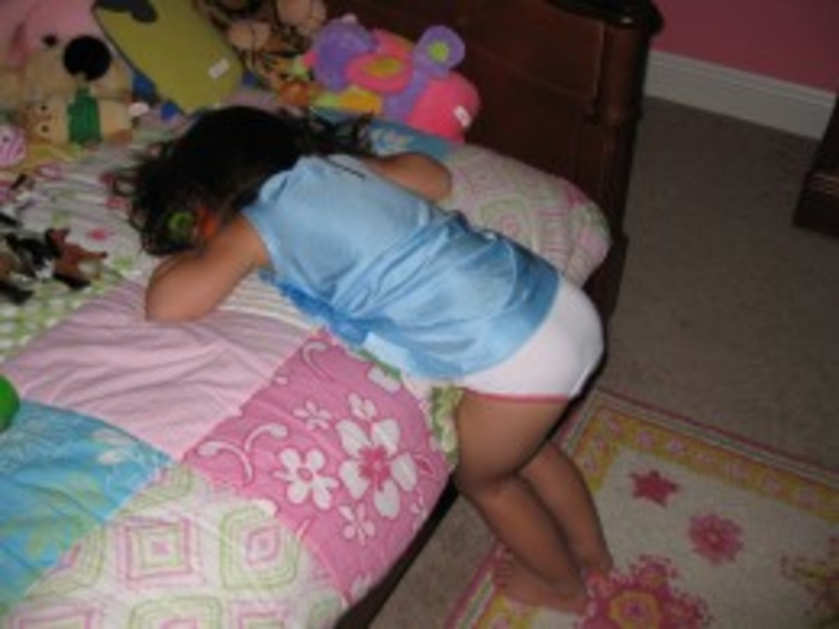 She clearly missed her sleep window - and fell asleep standing while playing with toys on her bed!