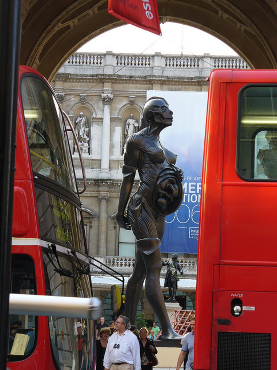 This is the 'Virgin Mother' statue in the Royal Academy, London (2005). A similar 66ft bronze statue by Damien Hirst, named 'Verity', has been installed at the harbour of Ilfracombe in Southern England (2012).
