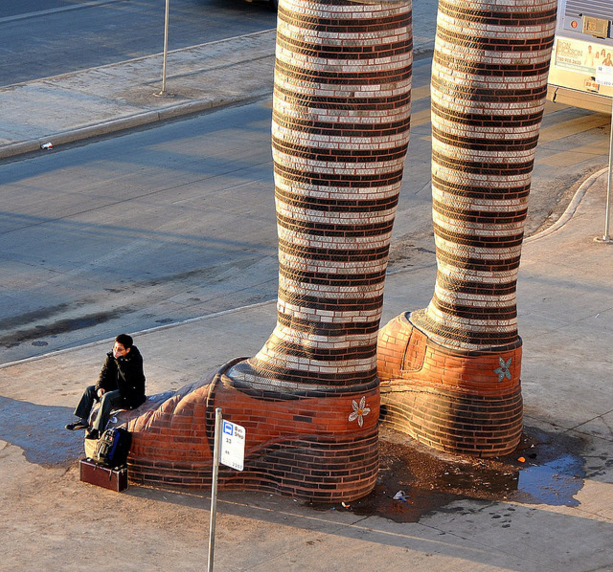 This sculpture is made of bricks and each leg is 20 feet tall. It is located in the middle of Southgate Transit Centre, Alberta (Canada).