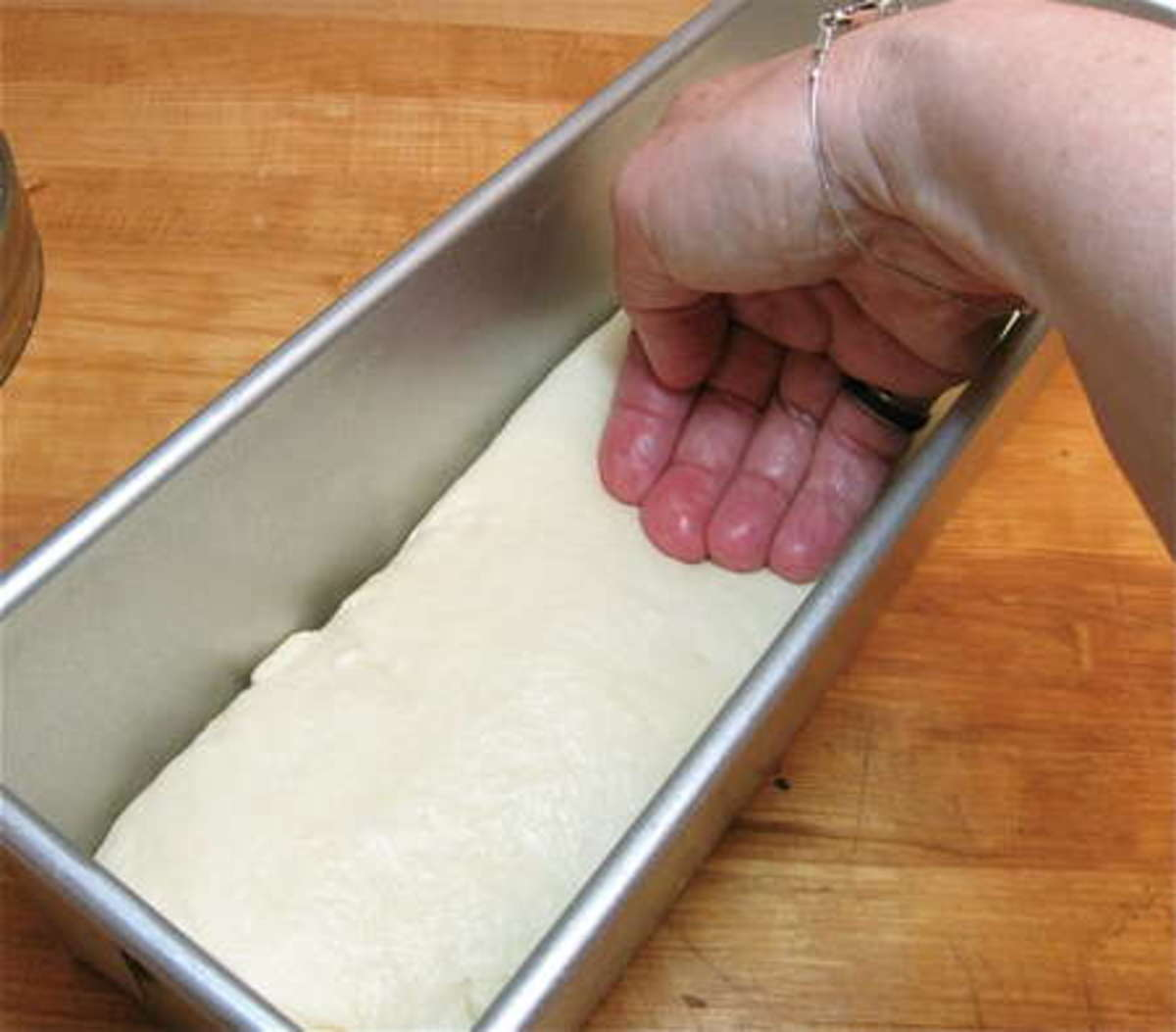 Gently place your punched down bread dough into the loaf pan and shape it a bit, be sure the seam side is on the bottom..