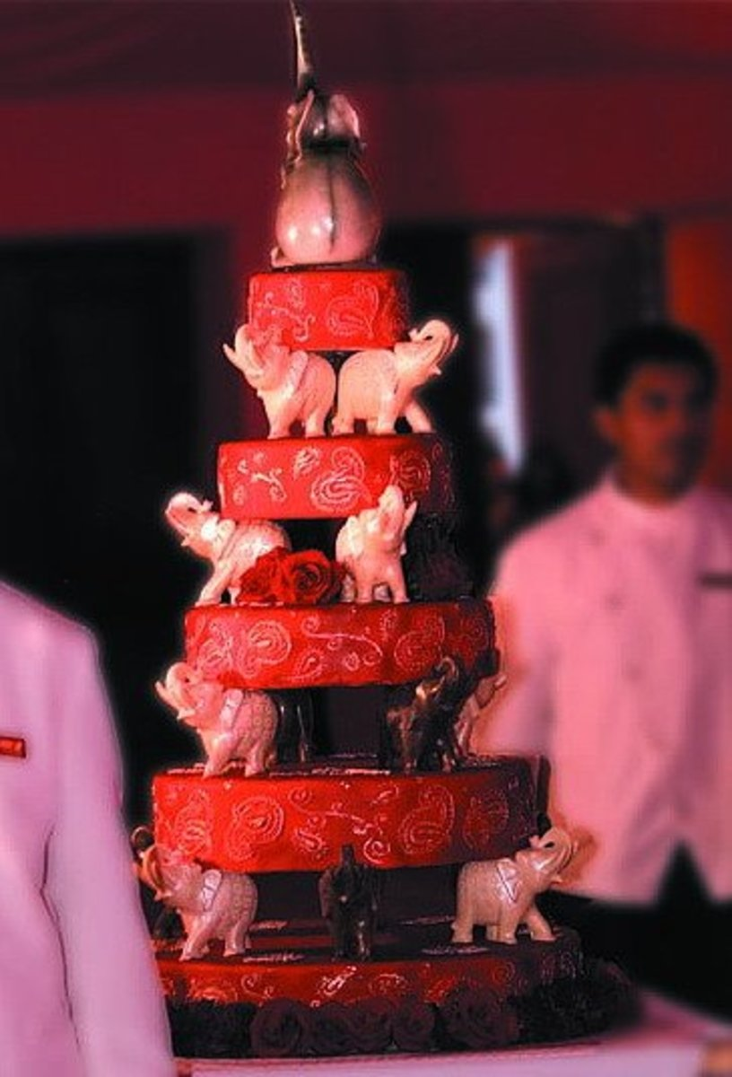 Indian themed wedding cake with elephant figurines.