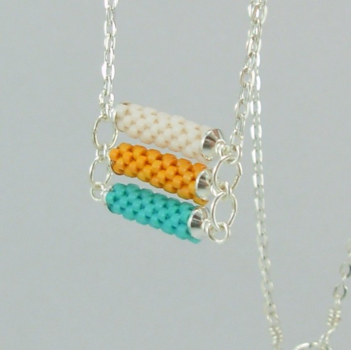 3 tier Beadwoven necklace in turquoise, orange and white: Combine several beaded beads with wire work to create stunning pieces like this one.